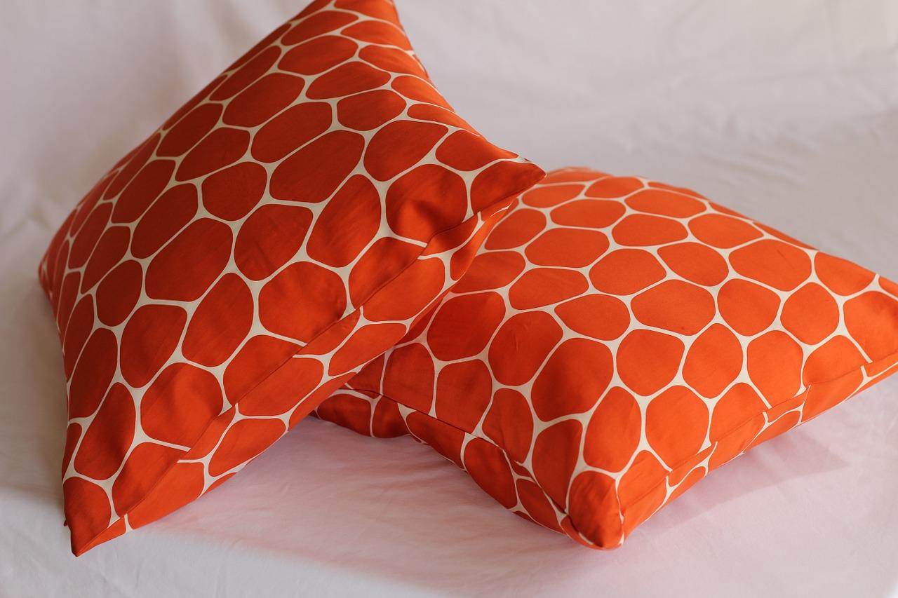 Two orange pillows laying down