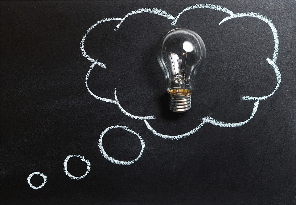 A thought bubble with a light bulb in it on a blackboard.