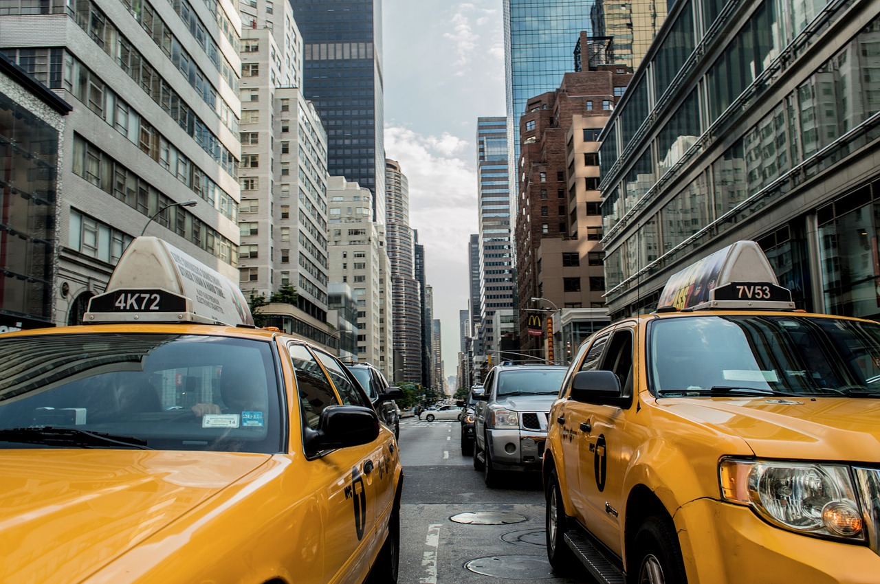 A New York Street. Some Taxi Vehicles Are At The Forefront, While Buildings Where One May Find An Apartment Stand At The Edges Of The Photo.