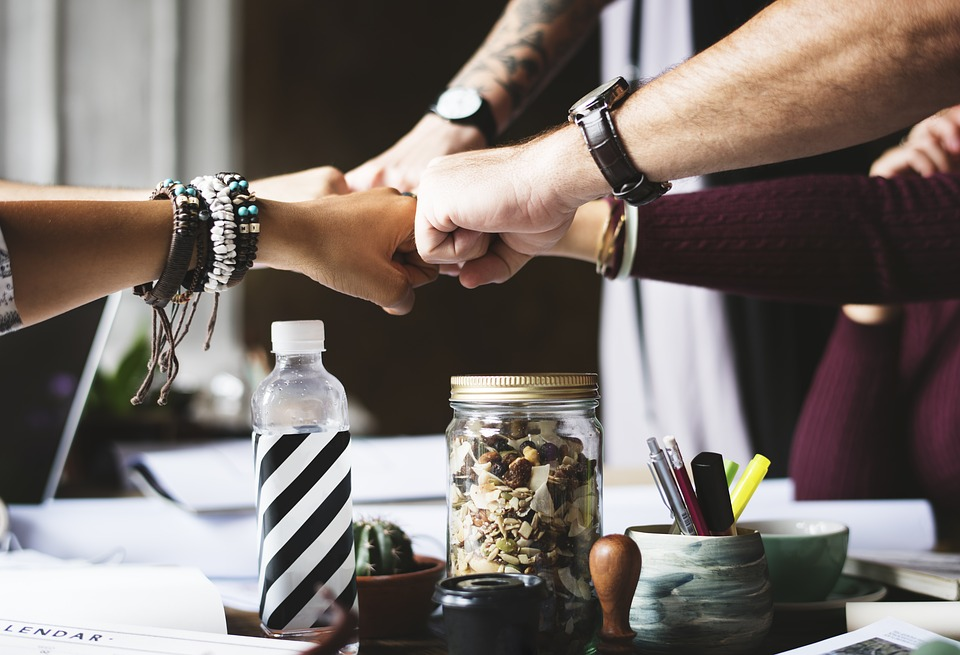 A group of people joining hands because the right company is necessary to stay safe when studying abroad.