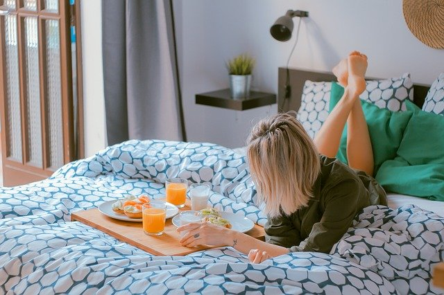 A woman laying in bed and eating - moving in with a new roommate can be tough because of the different habits