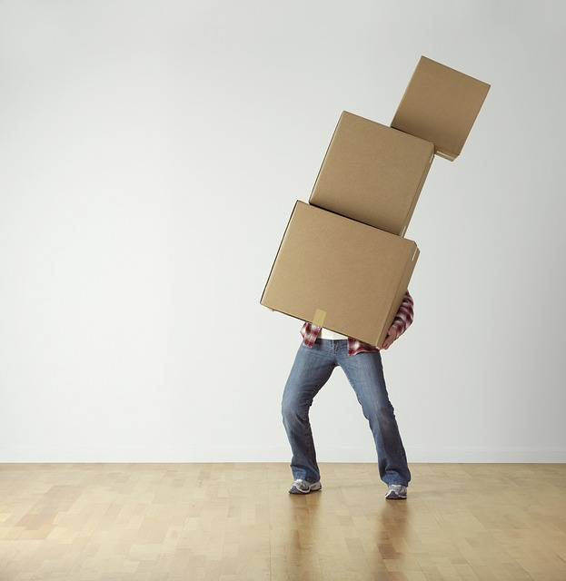 A Man Carrying A Pile Of Cardboard Vboxes After Solving The Dilemma Cardboard Boxes Vs. Plastic Boxes.