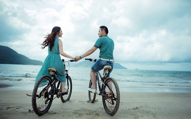 A couple riding bicycles and holding hands on the beach.