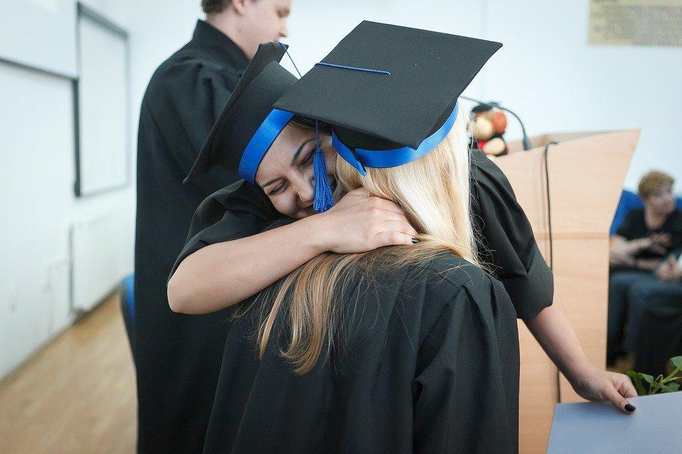 Two girls in graduation caps hugging.