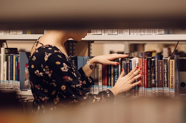 A Woman Looking At Some Books On A Shelf At The Library.