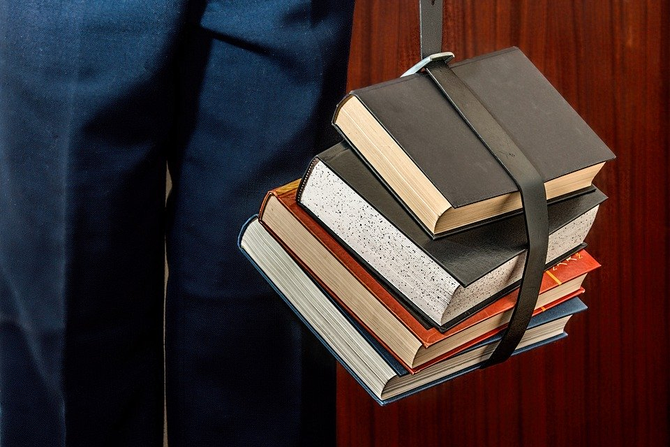Books wrapped with a belt and carries by someone.
