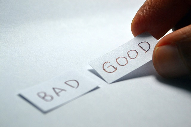 A Person Putting Two Pieces Of Paper Say Good And Bad Together.