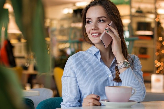 A young girl having a coffe at a cafe and talking on the phone.