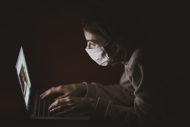 A girl with a face mask using a laptop.