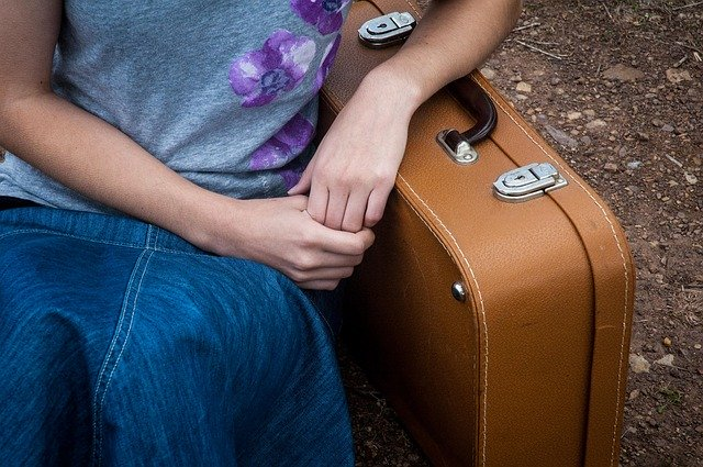 A person sitting next to a suitcase.