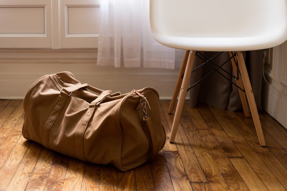 A packed brown duffel bag placed on the floor next to a white chair.