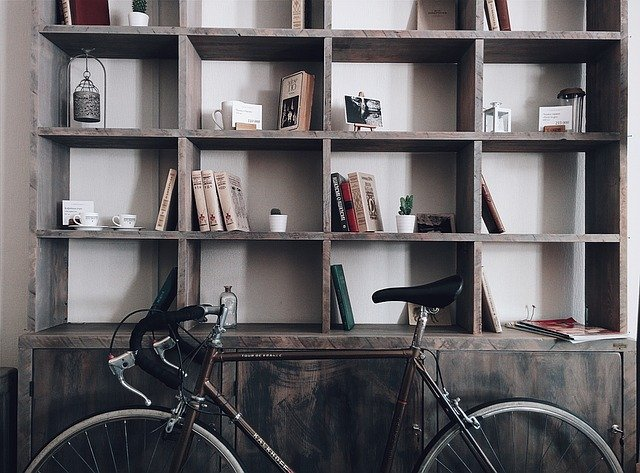 Bicycle leaning on a rustic bookshelf