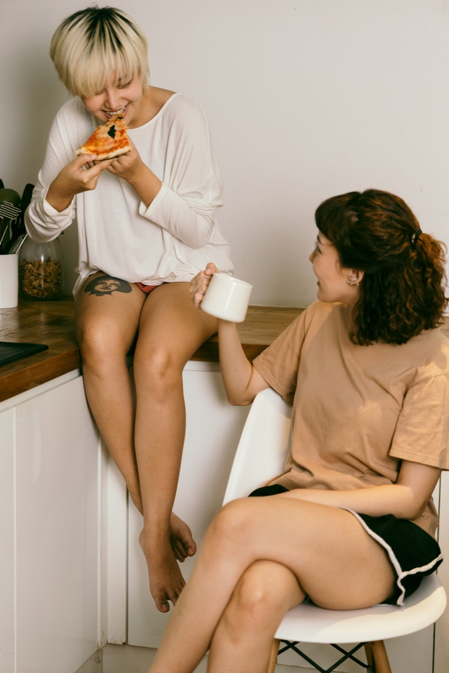 There are two girls sitting together and smiling. One of them is eating pizza, and the other is holding a mug.