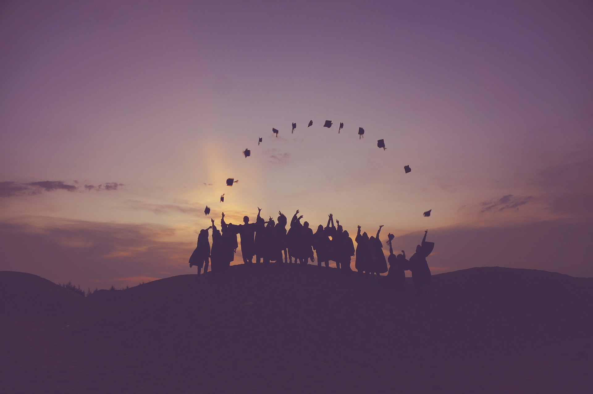 A group of students throwing their college caps in the air.