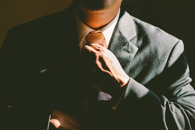 A man putting on a tie.