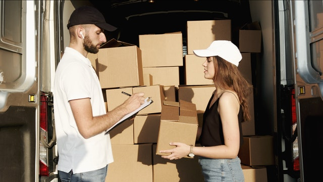 A man and woman packing boxes while involved in the process of Japanese students moving to the US