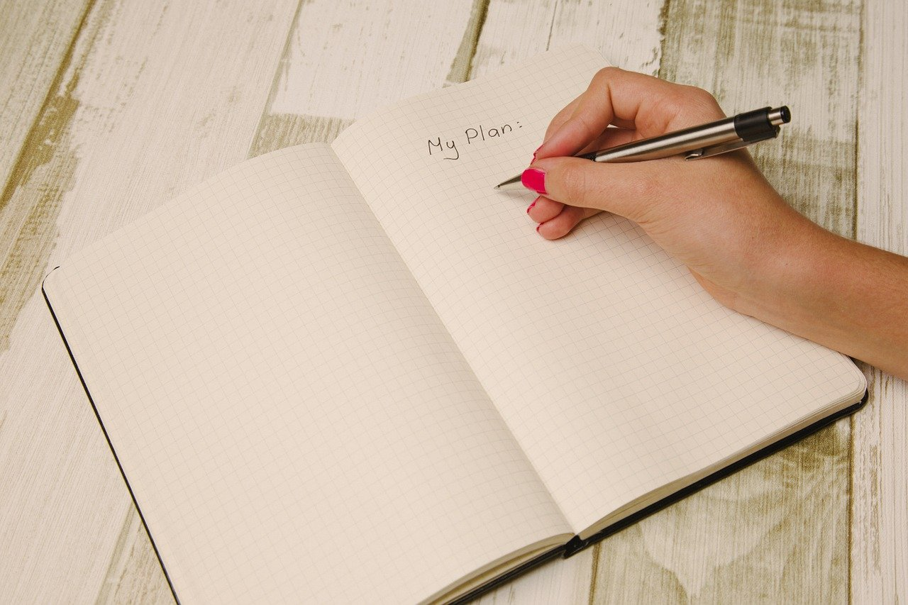 A girl writing a plan in a notebook.