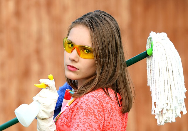 A woman with cleaning equipment is avoiding mistakes college students make when moving.
