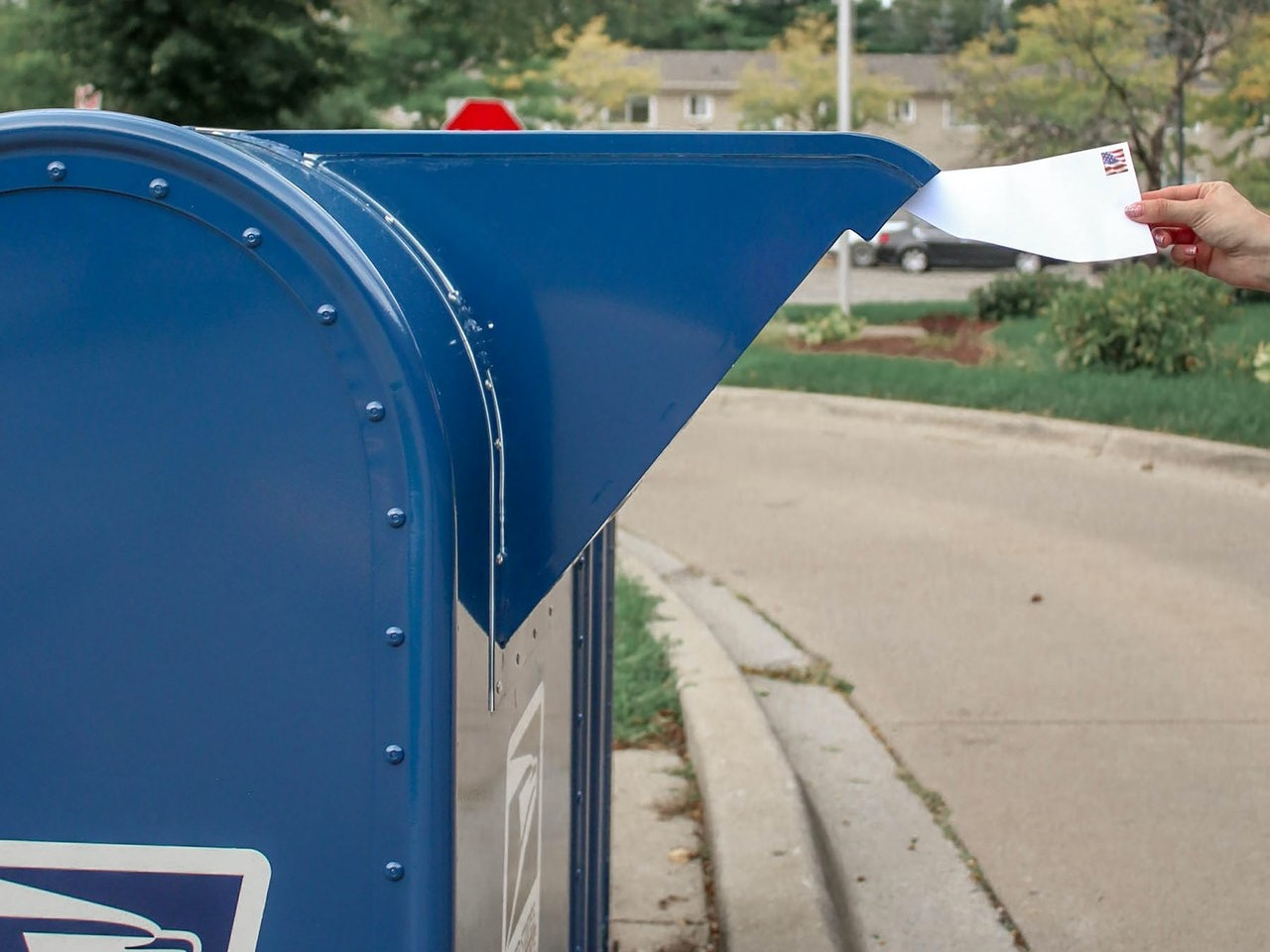 A man putting a letter in a USPS mailbox.
