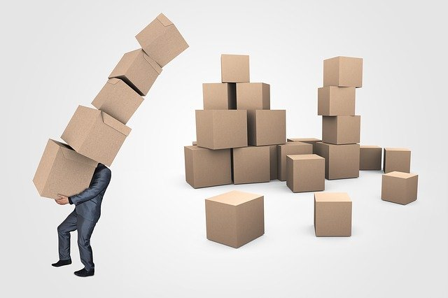 A man, carrying moving boxes.