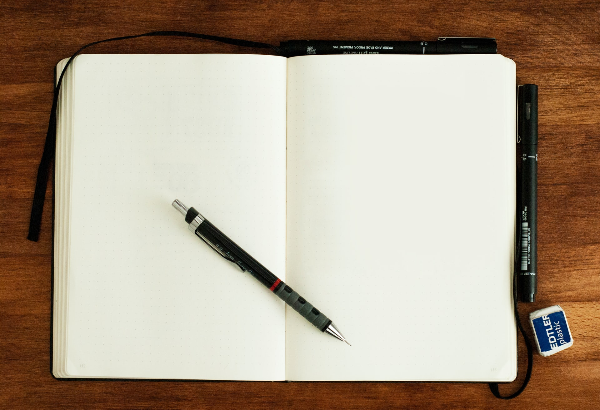 An open notebook with a pencil inside of it. Buying your first apartment in Austin will require some organizational skills. Write everything down.