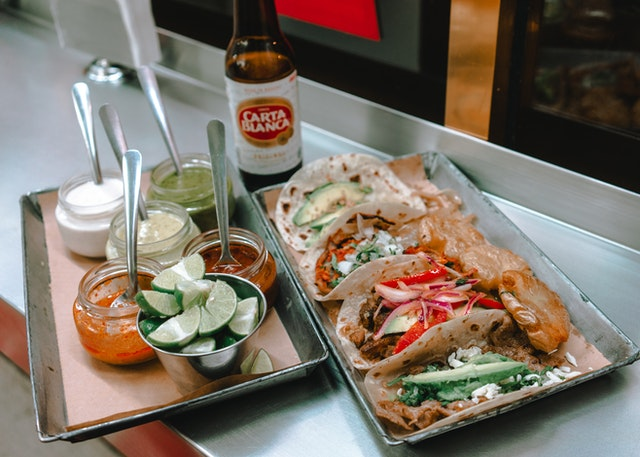 Food on a steel tray and a bottle of Carta Blanca symbolizing the dining scene that everyone moving in New Jersey as a student love